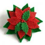 handgemaakte haarbloem in de vorm van een kerstster van glitter wolvilt met hulstblaadjes
